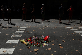 People walk near an impromptu memorial a day after a van crashed into pedestrians at Las Ramblas in Barcelona