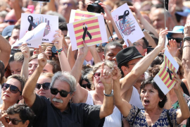 People hold banners as they observe a minute of silence in Placa de Catalunya, a day after a van crashed into pedestrians at Las