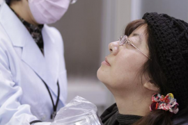 Sato, from Date in Fukushima, receives a screening test for signs of nuclear radiation from a doctor at a welfare centre in Yone
