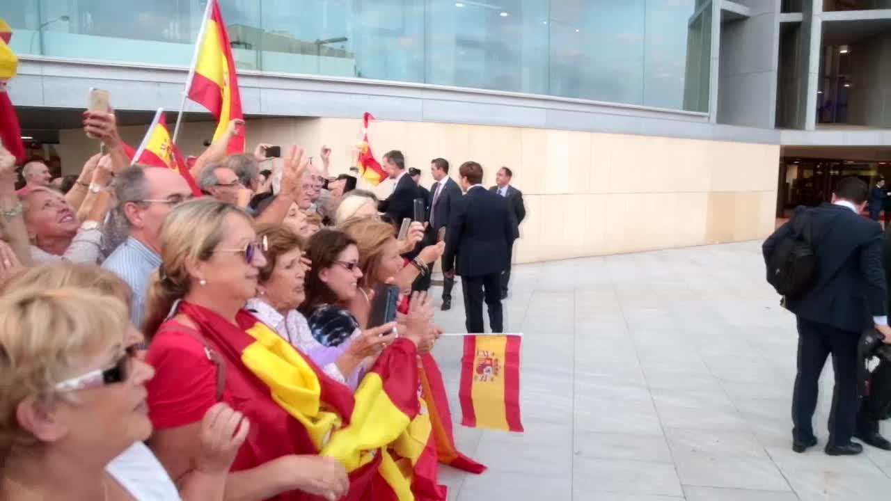 El Rey saluda al llegar al Palacio de Congresos a un grupo de personas con banderas españolas