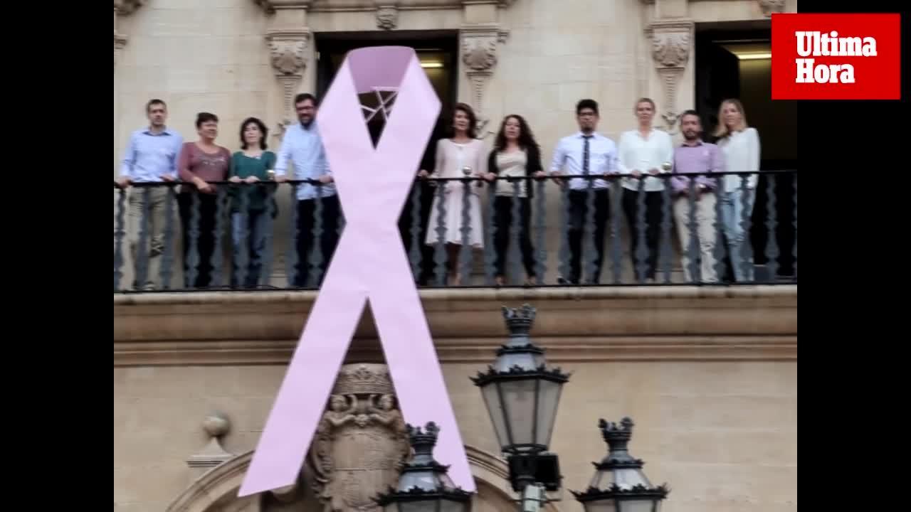 Cort cuelga un gran lazo rosa en la fachada del ayuntamiento