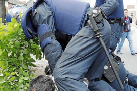 A man is detained by riot police during disturbances in north Dublin