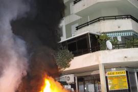 Arden dos contenedores y un coche aparcado junto a ellos en Son Rapinya