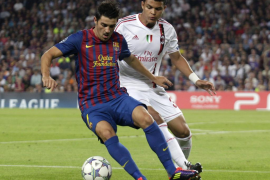 Barcelona's Villa is challenged by AC Milan's Silva during their Group H Champions League soccer match in Barcelona