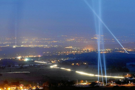 File photo of spotlights aimed at the sky above ground along the path of underground ring of LHC of CERN in Geneva