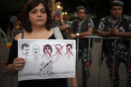 A Lebanese activist carries a caricature as Lebanese policemen stand guard in Beirut
