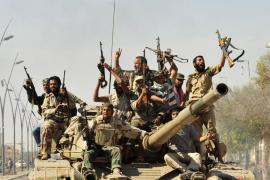 Anti-Gaddafi fighters celebrate the fall of Sirte in the town