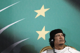 File photo of Libyan leader Muammar Gaddafi looking on as Italy's Prime Minister Silvio Berlusconi gives a speech in Rome