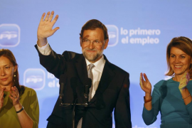 Spain's People's Party leader Rajoy acknowledges supporters next to his wife Elvira and party's secretary-general Cospedal after