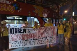 Los CDR de Mallorca despliegan una pancarta en un bus turístico para denunciar la masificación turística