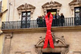 Un lazo rojo en la fachada de Cort para el Día Mundial del SIDA