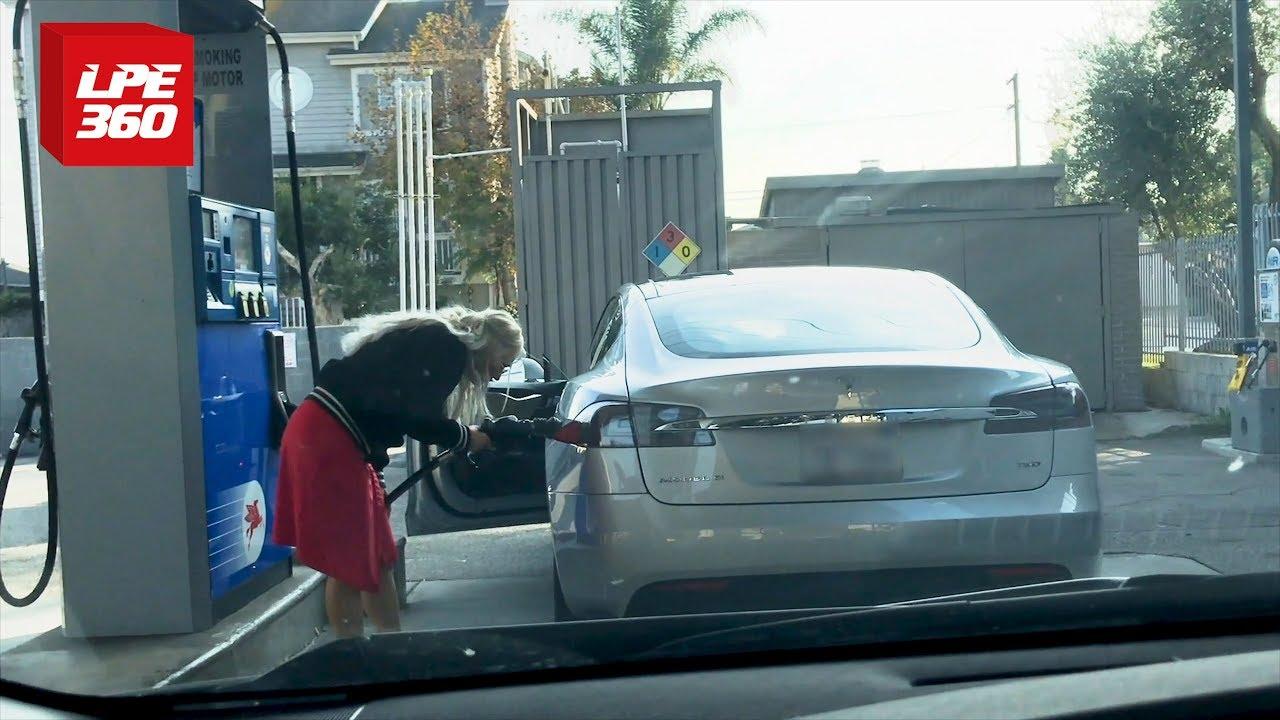 Una mujer intenta poner gasolina en un Tesla