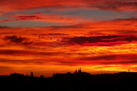 Cielo anaranjado, la catedral de fondo y fuegos artificiales