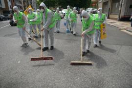 Un grupo de personas limpia las calles de Miravalles tras el acto de Rivera