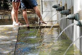 Turistas refrescándose en una fuente
