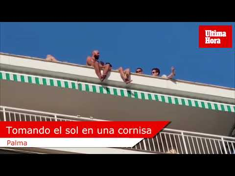 Unos turistas toman el sol en la cornisa de un edificio de Palma
