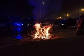 Manifestantes encienden una hoguera ante el cordón policial en el Aeropuerto de Barcelona
