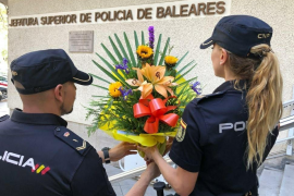 Una ciudadana entrega en la Policía Nacional de Palma un ramo de flores para los agentes que trabajan en Cataluña