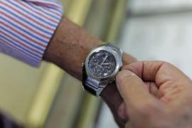 Un hombre mueve la manecilla del reloj para cambiar la hora