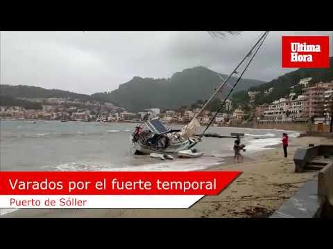 Tres jóvenes varan con su embarcación en la playa de Sóller
