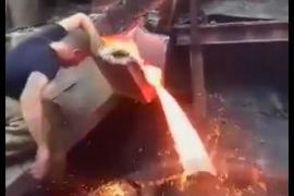 Un obrero mete la mano en metal fundido