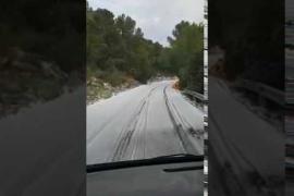 La intensa granizada cubre de blanco la carretera de la Cala de Sant Vicent